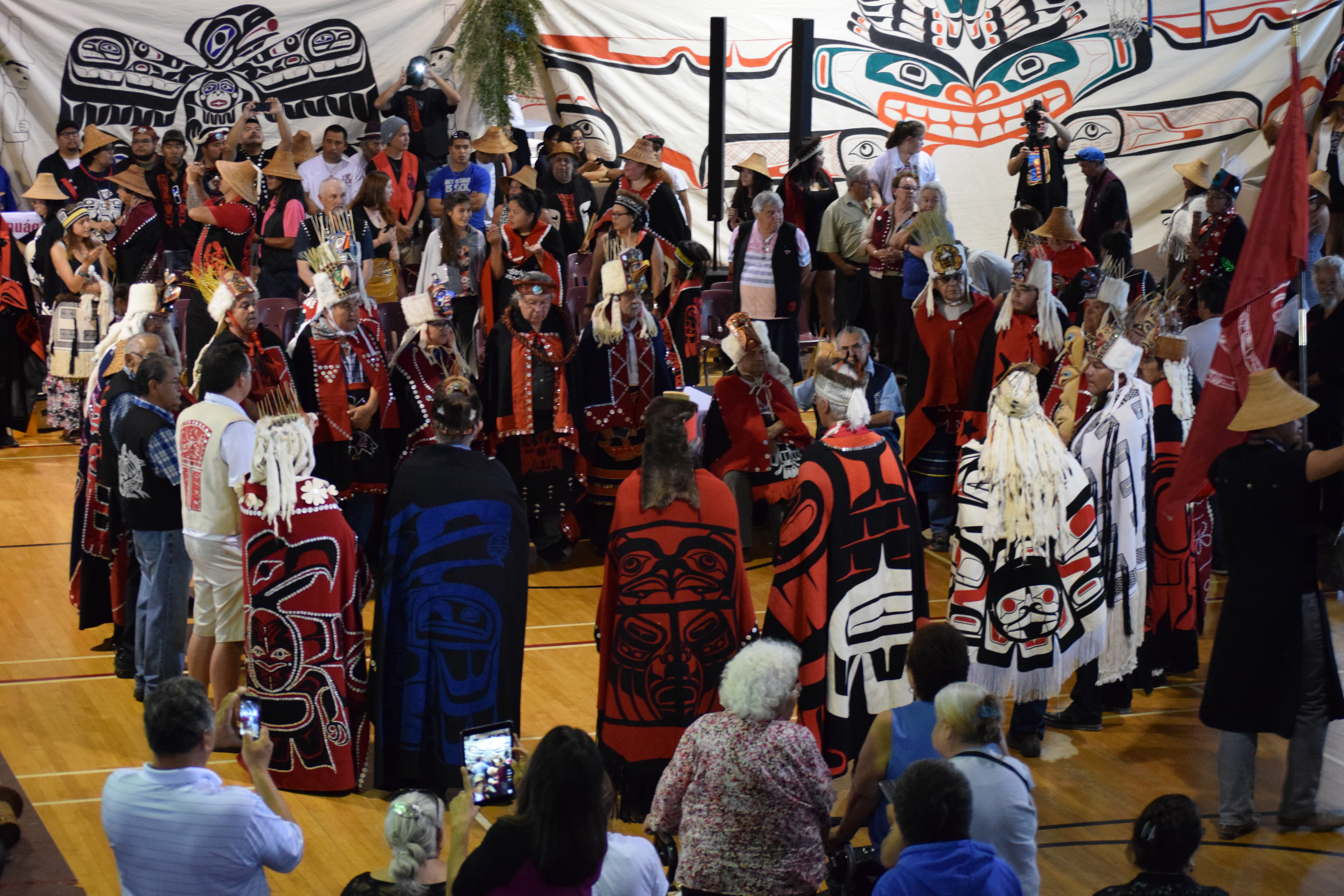 2 Haida and Heiltsuk hereditary leaders meet face to face in the centre of the potlatch floor