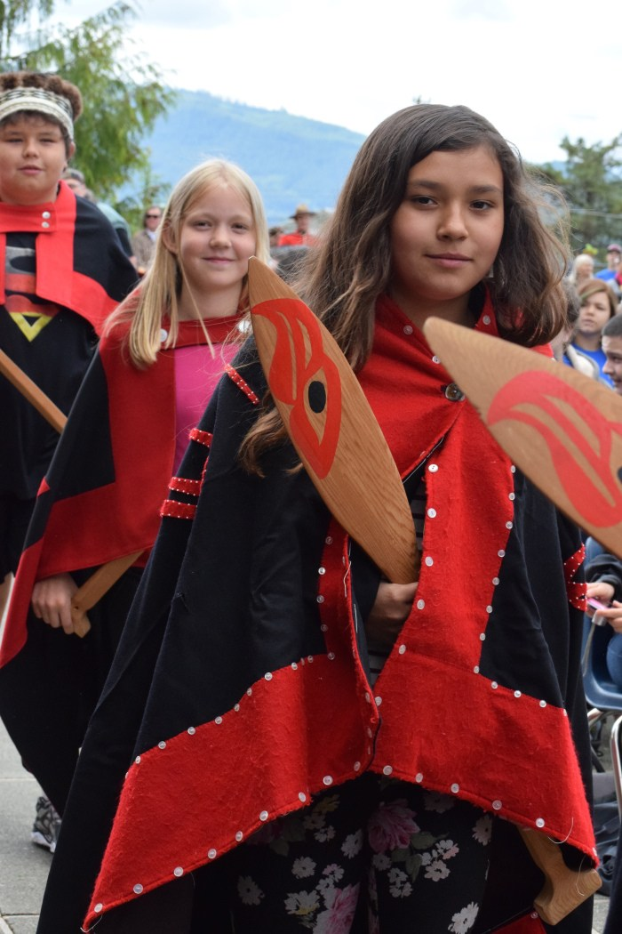 Children recognize the raising of two poles at Queen Charlotte Secondary School in May. Photo: Tawla Jaad
