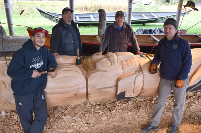 A team of carvers display their work at K_ay Llnagaay in October. L-R: StllnG_a (Tyler York), Laada (Tim Boyko), St'inll (Garner Moody, head carver) and Kwakyans (Tony Greene)